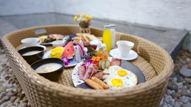 vídeos y material grabado en eventos de stock de desayuno flotante chica asiática desayuna junto a la piscina. - exotismo