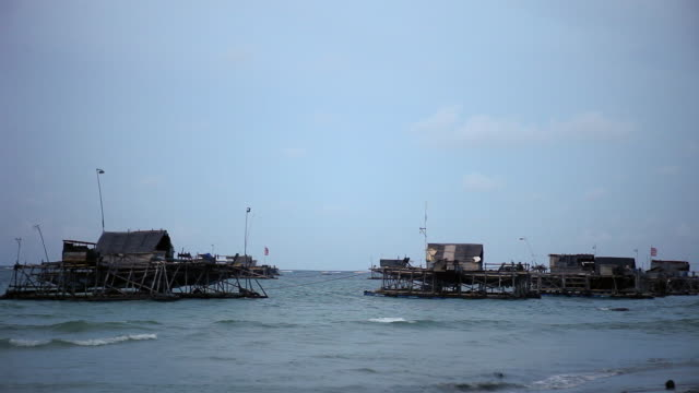 vídeos de stock e filmes b-roll de ws floating fishing huts that are towed out  to sea and their nets lowered - pontão