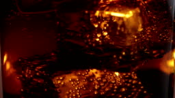 Floating ice cubes in a glass of Cola - close up macro shot in slow motion