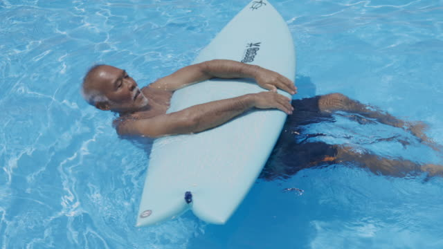 floating senior man on the water with surfboard - solo giapponesi video stock e b–roll