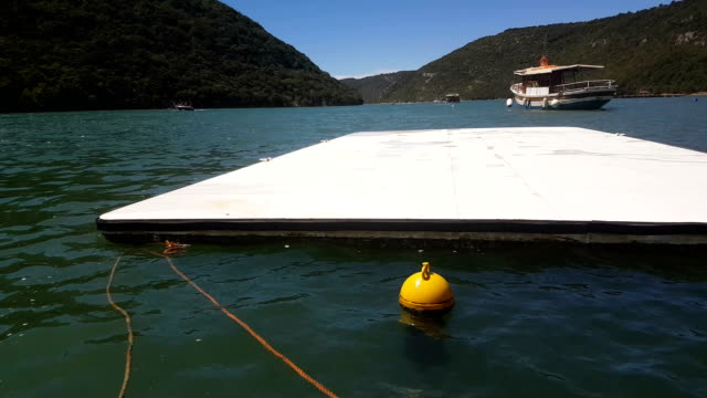 floating water platform in a beautiful exotic azure bay - floating moored platform stock videos & royalty-free footage