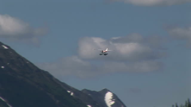 a floatplane glides away from a lake toward a mountain. - プロペラ機点の映像素材/bロール
