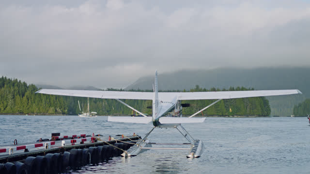 a floatplane harbors at a tofino dock and sways in the wind as a boat passes in the inlet. - inlet stock videos & royalty-free footage
