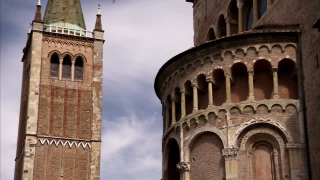 a flock of birds flies around the parma cathedral and baptistery. available in hd. - parmigiano video stock e b–roll