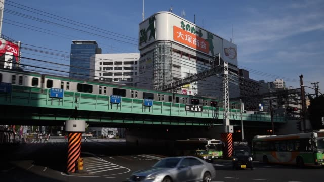 flock of pigeons fly overhead in the shinjuku district of tokyo, japan, on thursday, may 14 a metro train travels along an overpass to the right, a... - general view stock videos & royalty-free footage