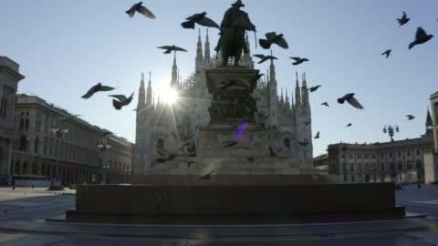 在2020年大流行封鎖期間,在維托里奧·伊曼紐爾二世雕像前大教堂(大教堂)的大教堂前飛舞的鴿子群。早上空蕩蕩的城市。 - 義大利文化 個影片檔及 b 捲影像