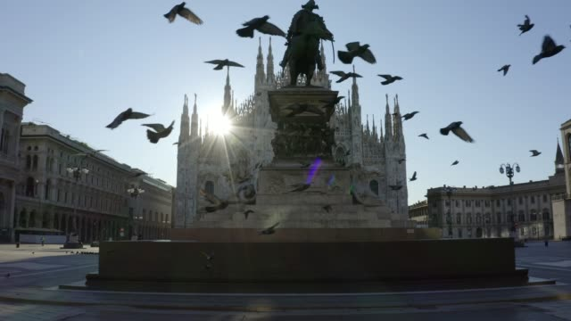 vídeos de stock e filmes b-roll de flock of pigeons flying in front of the duomo di milano (milan cathedral) in piazza del duomo (duomo square) in front of the statue of vittorio emanuele ii during the pandemic lockdown in 2020. empty city in the morning. - itália