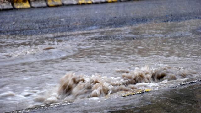 vídeos de stock, filmes e b-roll de inundação depois que a chuva está fluindo pelo ralo na estrada - drenagem
