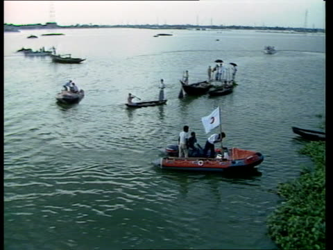 "flood relief measures; bangladesh two men sitting aboard rnli rubber boat as along track side ""red crescent"" flags fying from rnli boats... - flag of bangladesh stock videos & royalty-free footage"
