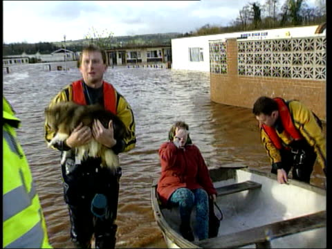 Devon Dawlish Warren Fire men pulling boat towards containing people rescued from flooded caravan park ZOOM IN Boat containing caravan park residents...