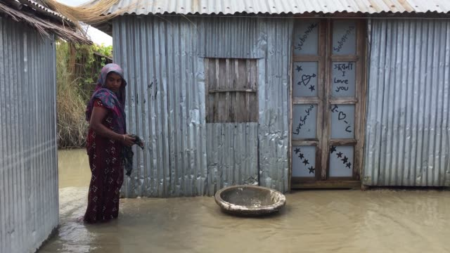A flood victim woman is cleaning her house which was badly affected by flood in Gaibandha Bangladesh August 19 2017