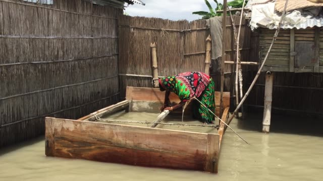 A flood victim woman is cleaning her wooden bed which was under flood water for many days in Gaibandha Bangladesh August 19 2017