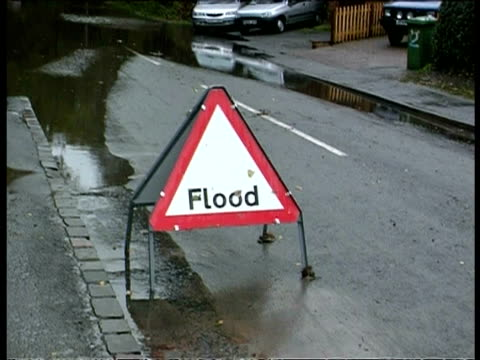 MCU Flood warning sign, zoom out and tilt up to flooded road blocked by fallen tree, UK