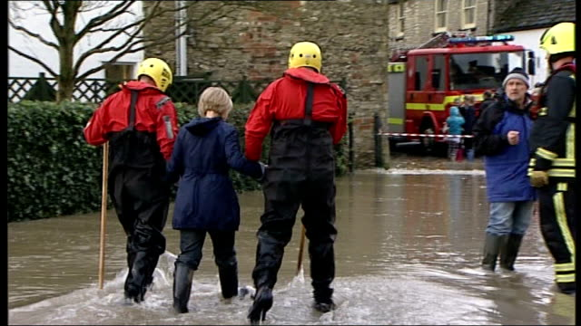stockvideo's en b-roll-footage met flood warnings in place as storm batters britain wiltshire malmesbury flooded road rescue workers and woman wading along through flood water jenny... - wiltshire