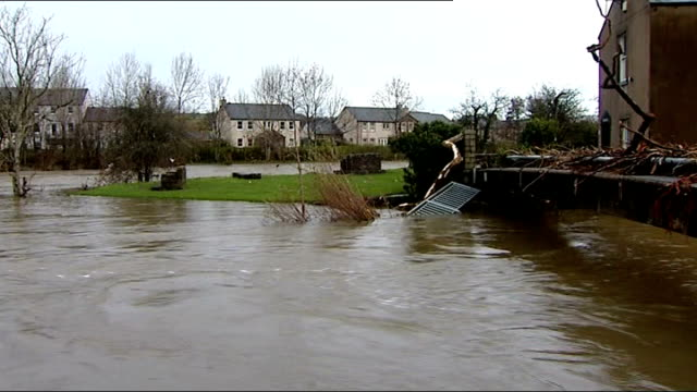 flood water flowing swiftly stone cottages and steps in flooded street damaged car christmas tree standing askew in main street 'merry christmas'... - tinsel stock videos & royalty-free footage