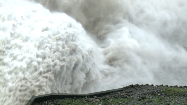 flood water flows down spillway of hydroelectric dam - steps stock videos & royalty-free footage