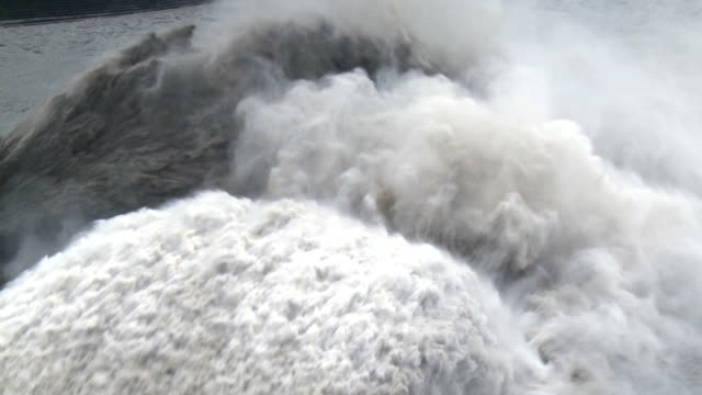 flood water flows down spillway of hydroelectric dam - dam stock videos & royalty-free footage