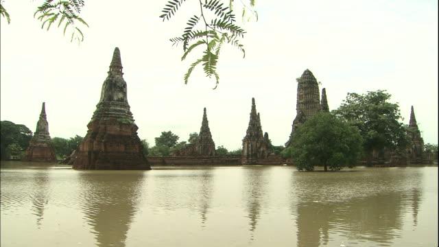 flood water flows through the ruins of wat chaiwatthanaram. - ワットチャイワタナラム点の映像素材/bロール