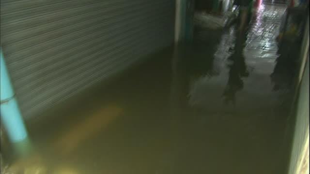 flood water gushes across sandbags through a bangkok shopping promenade - 2011 stock videos & royalty-free footage