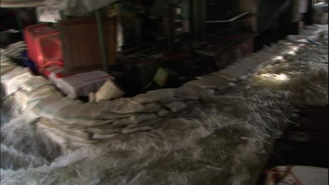 flood water in bangkok surges past stacks of sandbags - 2011 stock videos & royalty-free footage