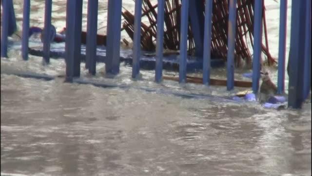 Flood water in Thailand flows under a gate