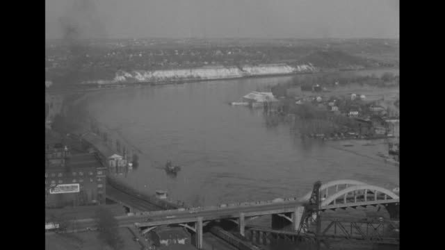 Flood water moving pan up to factory buildings with smokestacks city in bg / Missouri River bridge in bg railcars and tracks to side / same shot...