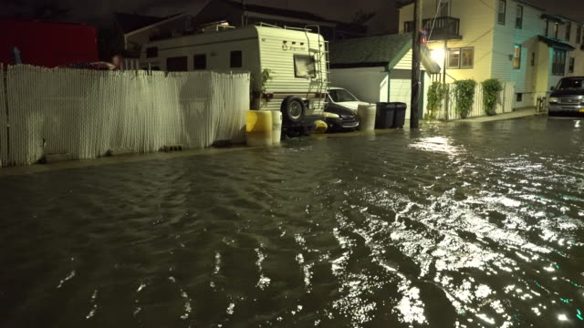 Flood waters as a result of tidal surge inundate a residential street at night in Queens New York as Jamaica Bay overflows it's banks during the...