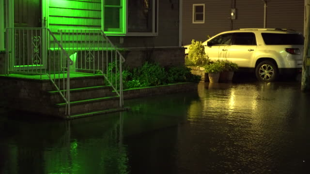 Flood waters begin to creep up the steps and driveway of a residential home in Queens New York as Jamaica Bay overflows it's banks during the high...
