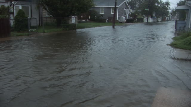 flood waters begin to inundate a residential street, and surround homes as hurricane irene makes landfall in the new york city area. - hurricane irene stock videos & royalty-free footage