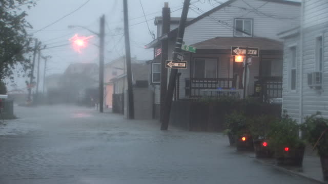 flood waters, getting deeper by the minute, begin to flow into the town of broad channel, ny near the rockaways as hurricane irene makes landfall in... - hurricane irene stock videos & royalty-free footage