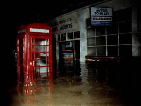 flood waters have submerged the high street in molesey - telefonzelle stock-videos und b-roll-filmmaterial