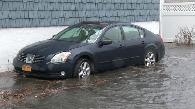 Flood waters surround a vehicle during a powerful nor'easter in the town of Broad Channel New York