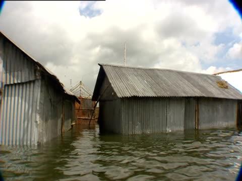 stockvideo's en b-roll-footage met flood waters surround shacks in bangladesh - omgeven