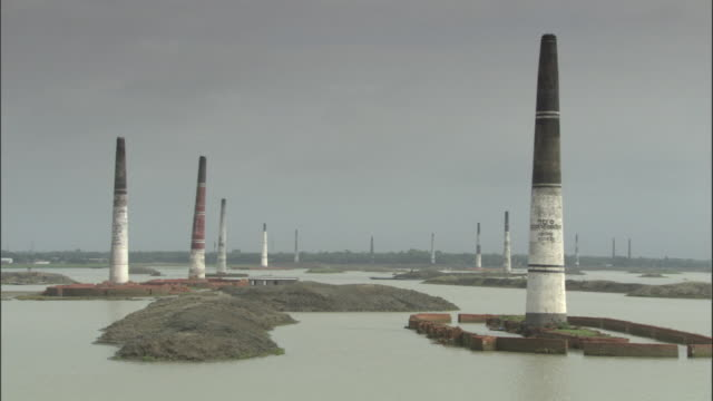 vídeos de stock, filmes e b-roll de flood waters surround towers of brick kilns in ashulia bangladesh. available in hd. - bangladesh