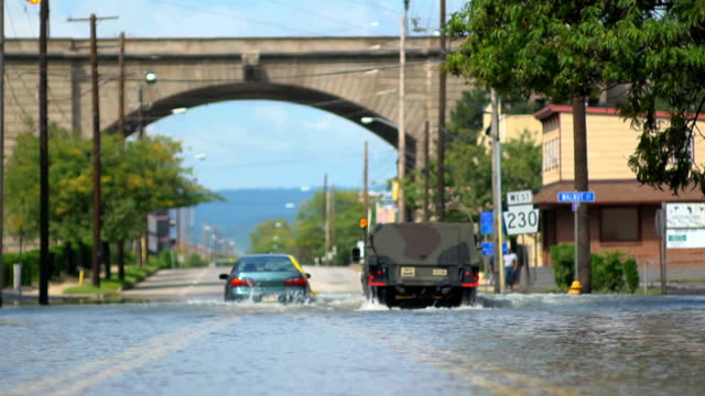flooded car under arch wide shot with military vehicle - tropical storm stock videos & royalty-free footage