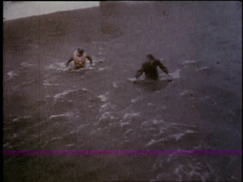 vidéos et rushes de flooded residential area, men wading through water / new york city, new york, united states - 1957