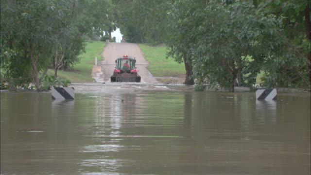 zo flooded river covering a road while a tractor is working to remove water / adelaide river, northern territory, australia - adelaide river stock videos & royalty-free footage