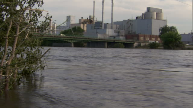 A flooded river rushes under a bridge and past buildings in Cedar Rapids, Iowa.