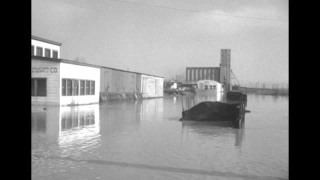 Flooded street buildings on either side / MS warehouse with sandbags stuffed all around it and at windows and in delivery dock / VS flooded streets /...