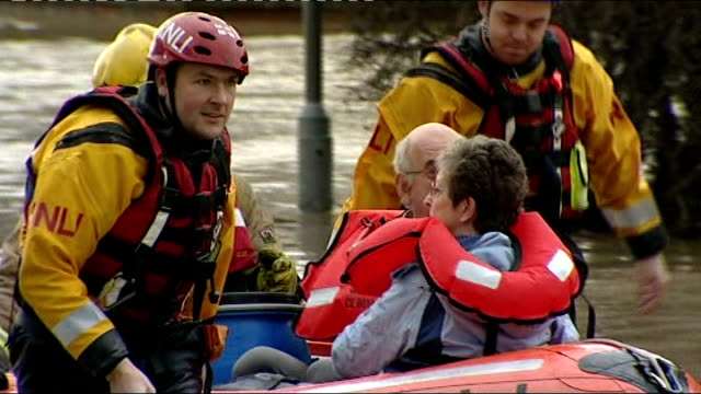 flooding across england and wales; fire engine along firefighters helping woman out of fire engine rnli workers pulling people along in lifeboat... - retter rettungsaktion stock-videos und b-roll-filmmaterial