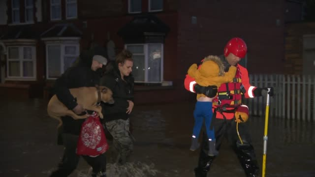 vídeos y material grabado en eventos de stock de flooding across parts of england after a month's worth of rain falls in one day england south yorkshire doncaster rescue worker carrying child... - yorkshire