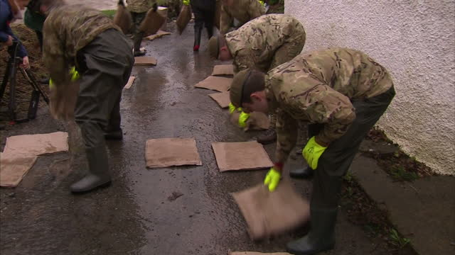 Flooding affects the North of England Scotland Shows exterior shots soldiers unpacking placing out absorption pads by riverside on December 30 2015...