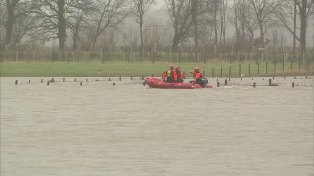 Flooding affects the North of England Scotland Shows exterior shots fire engines pumping water away from road emergency rescue team in rubber dinghy...