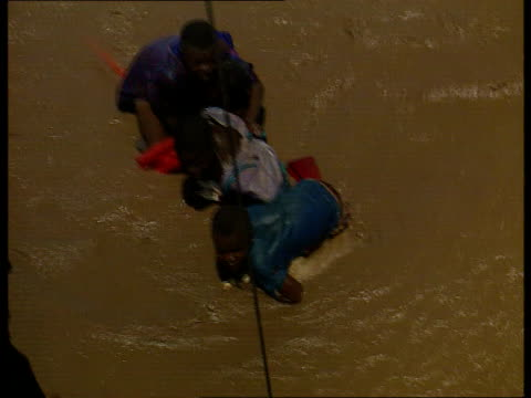 vídeos de stock e filmes b-roll de flooding aftermath lib boy along with 3 others stranded in floodwater air view helicopter winchman martin randellhoff being lowered to rescue the... - moçambique
