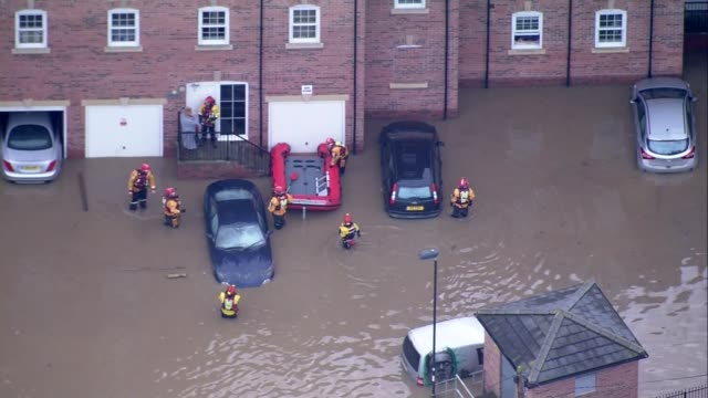 flooding and evacuations in yorkshire air views resuce workers wading through waistdeep water with dinghy / along toward houses / residents evacuate... - waist deep in water stock videos & royalty-free footage