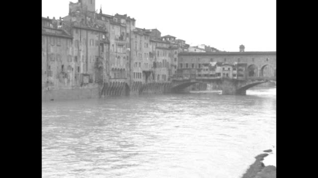 Flooding Arno River rushing under famous bridge Ponte Vecchio in Florence / people standing on porch of flooded building / soldiers poling boats down...