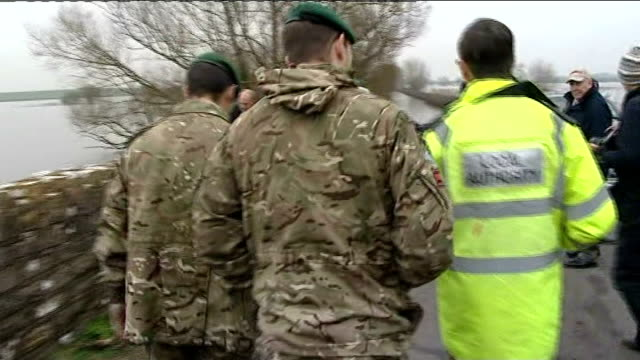 british troops in somerset levels more gvs flooded countryside / various of two soldiers inspecting flood conditions in country lane / flash on... - somerset levels stock videos and b-roll footage