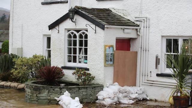 flooding caused by storm ciara at lake windermere in ambleside lake district uk with the wateredge hotel beer garden underwater - umbrella stock videos & royalty-free footage