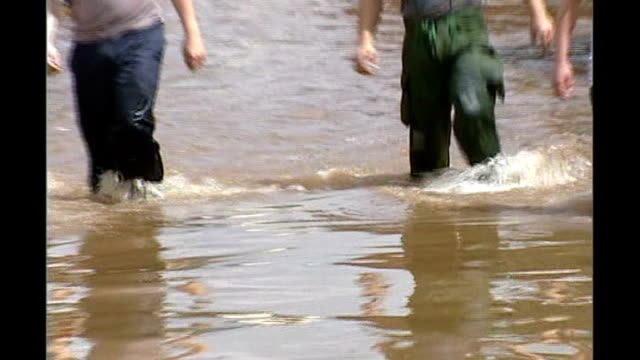flooding continues across northern england herefordshire tenbury wells ext people wading through flood water in high street back view woman holding... - tenbury wells stock videos and b-roll footage
