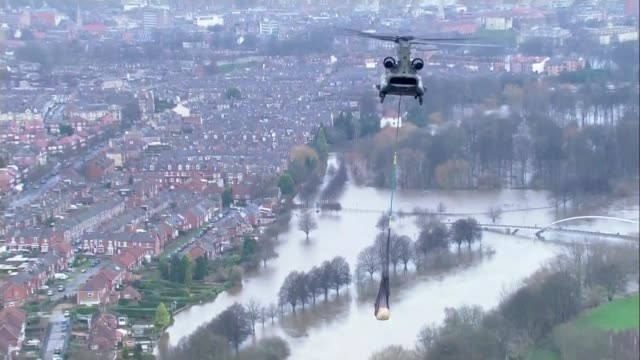 david cameron visits yorkshire / government flood policy questioned; england: yorkshire: york: ext air views / aerials raf chinook helicopter flies... - lowering stock videos & royalty-free footage